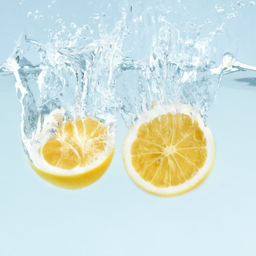 Citrus splash. Lemon halves splattering into clear water on blue background