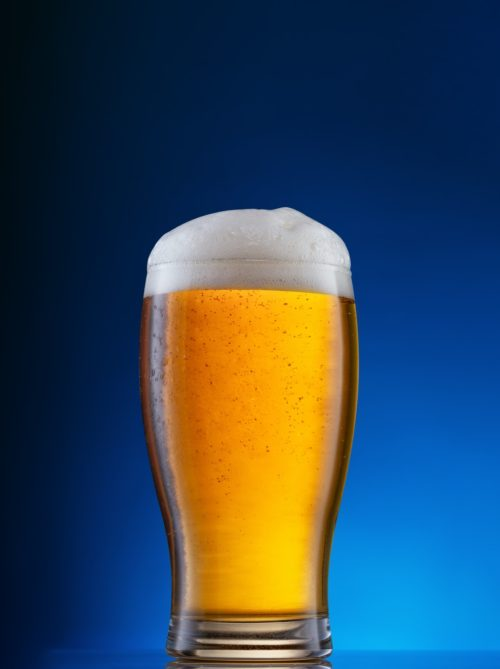 Glass with light beer on blue background
