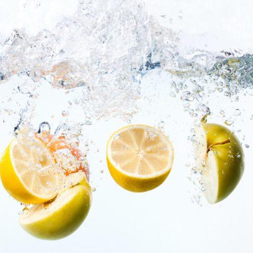 Half lemons and apples in water